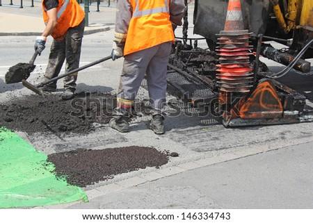 Workers on Asphalting paver machine during Road street repairing works - stock photo