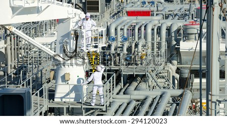 Workers on gas tankers, natural gas storage in the background. Refinery, oil and natural gas. Industrial - stock photo