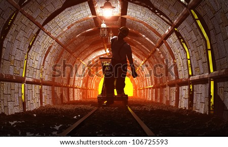 Workers pushing the cart in the mine. - stock photo