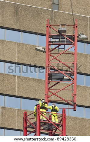 Workers reaching for a hoisted tower crane part - stock photo