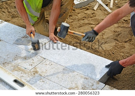 Workers tapping pavers into place with rubber mallets. Installation of granite paver blocks series with motion blur on hammers and hands. - stock photo