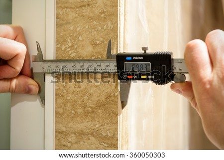Workers use a electric calipers during the construction of the home's interior - stock photo
