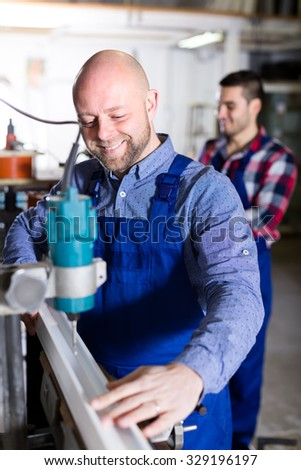 Workers using a lathe to cut window aluminum frames - stock photo