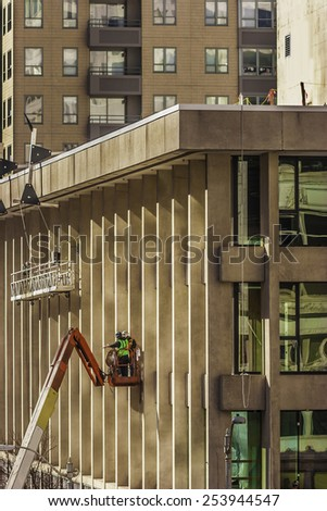 Workers wearing safety harnesses on Cherry Picker - stock photo