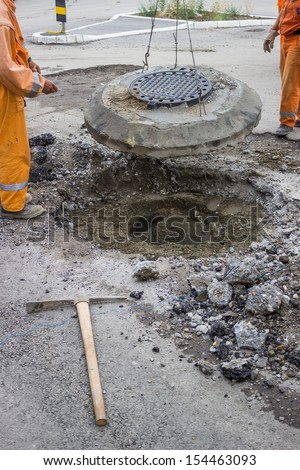 workers work on the replacement of cover slab with cast iron cover on the road  - stock photo