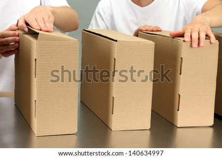 Workers working with boxes at conveyor belt, on grey background - stock photo
