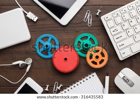 workflow and teamwork concepts with colorful gears different gadgets and office stationery on the wooden table - stock photo