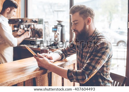 Working at coffee shop. Side view of young handsome man using his digital tablet while sitting at bar counter at cafe with barista at background - stock photo