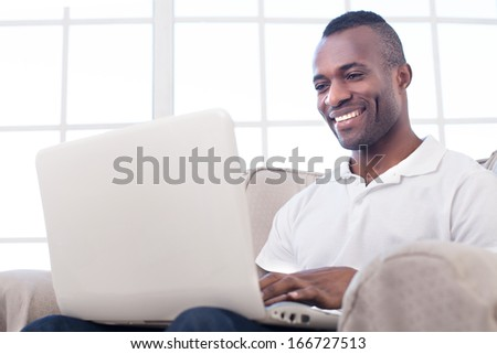 Working at home. Cheerful African man using computer and smiling while sitting on the chair - stock photo