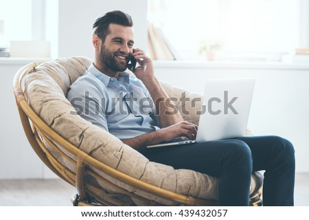 Working at home. Cheerful young handsome man working on laptop and talking on the mobile phone while sitting in big comfortable chair at home   - stock photo