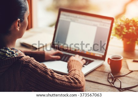 Working at home. Close-up image of young woman working on laptop while sitting at the rough wooden table  - stock photo