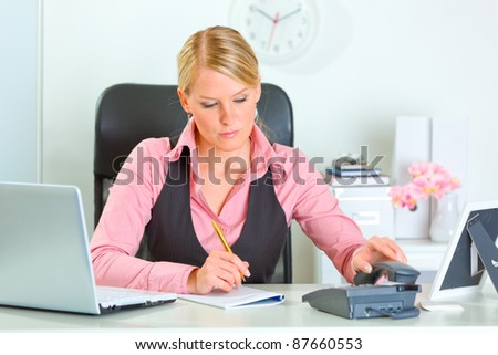 Working at office business woman picking up phone - stock photo