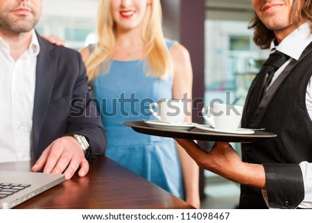 Working colleagues - a man and a woman - sitting in cafe working, the waiter serves coffee - stock photo