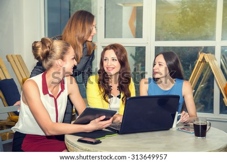 Working days in the women's team. Four young women - office staff. Discussion of joint work on the project. Female business. Women working in the office at the computer. Group of women. Toned image. - stock photo