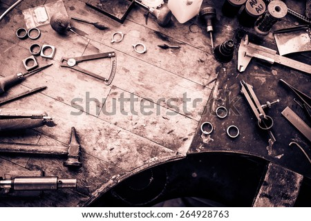 Working desk for craft jewelery making with professional tools. Grunge wooden table. View from above. Copy space. - stock photo