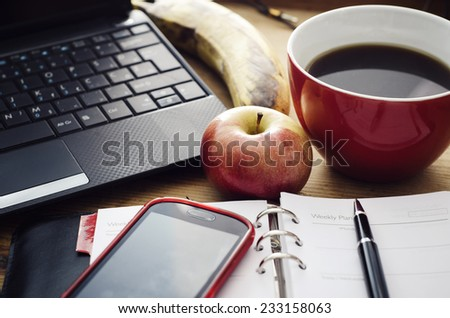Working desk in the morning with open planner, laptop, mobile phone and apple. - stock photo