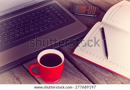 working desk with cup of coffee planner agenda laptop and mobile phone vintage morning photo - stock photo