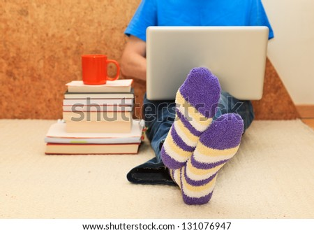Working from home. Man relaxing in bed using laptop, close up on male foots in socks. - stock photo