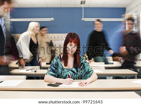 Working girl among moving pupils at the end of the Class - stock photo