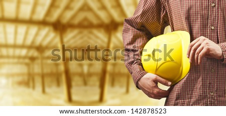 working hands without gloves holding a yellow hard hat close-up on background empty warenhouse background - stock photo