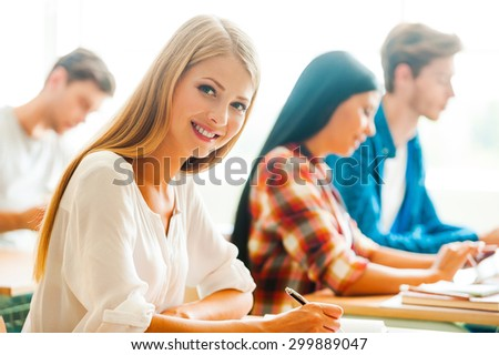 Working hard for good grades. Beautiful young woman writing and looking at camera while her classmates studying in the background  - stock photo