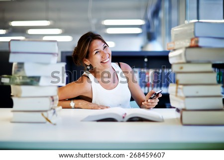 Working hard for great grades, asian smiling student girl sitting at the desk behind stack of books in university library, female teenager looking so happy with schooling, exam preparation - stock photo