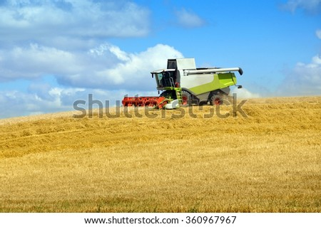 Working harvester on the yellow field with hay. - stock photo