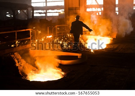 Working in a foundry. Workers looking down, red color is a reflection of the molten metal. Very high heat and purple fringing. See more images and video from this series. - stock photo