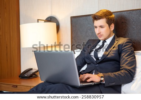 Working in hotel room. Confident young businessman in suit and tie working on laptop while sitting on the bed in hotel room - stock photo