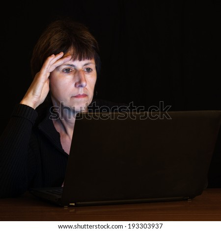 Working late - mature woman works, studies at night lit by laptop computer screen. - stock photo