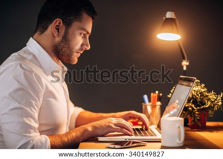 Working late. Side view of confident young man working on his laptop while sitting at his working place at night time - stock photo