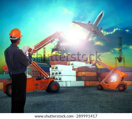 working man in logistic business working in container shipping yard with dusky sky and jet plane cargo flying above use for land to air transport and freight - stock photo
