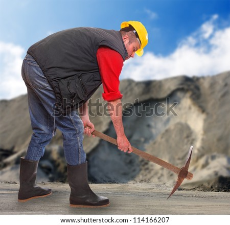 Working man with pick axe in a coal mine. Under construction concept. - stock photo