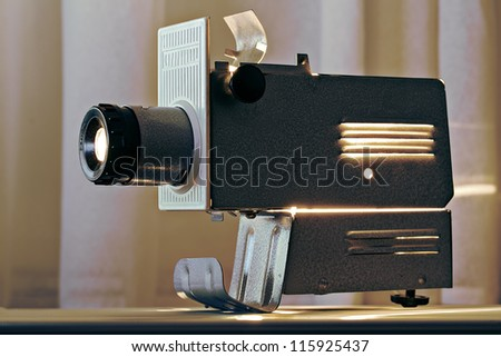 Working  metal projector on table top radiating heat - stock photo