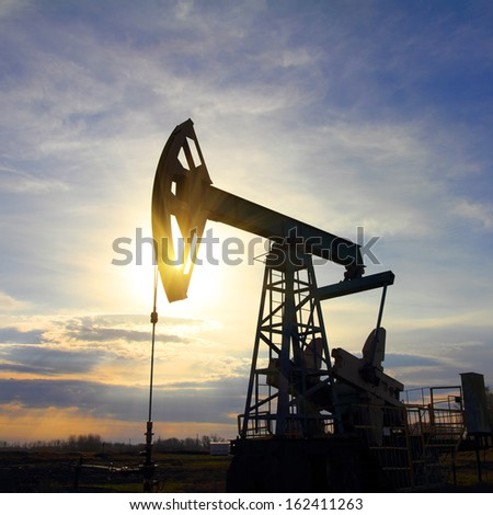 working oil pump at sunset - stock photo