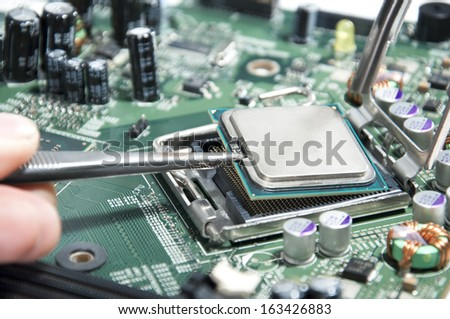 Working on computer motherboard - stock photo
