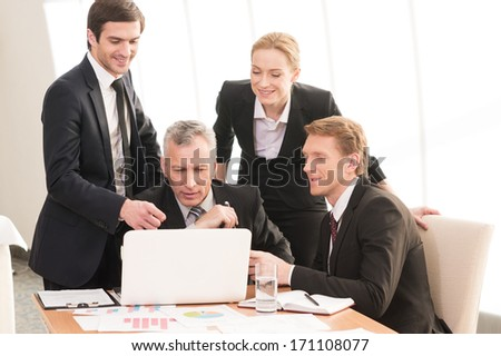Working on project together. Four smiling business people in formalwear discussing something while one of them pointing laptop - stock photo