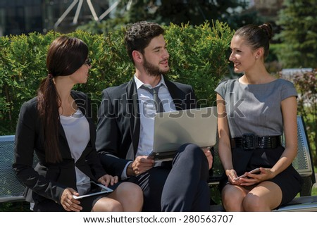 Working on successful project.  Three confident and motivated business partners are discussing business details of current projects. All are wearing formal suits. Outdoor business concept - stock photo