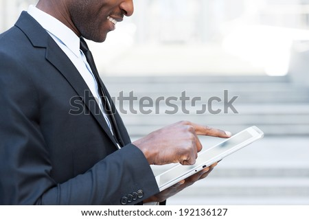 Working on tablet. Side view cropped image of African man in formal wear working on digital tablet and smiling while standing outdoors - stock photo