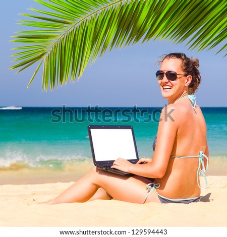 working on the beach. Woman is sitting with laptop with blank screen - stock photo