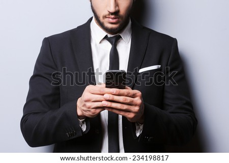 Working on the go. Close-up of young man in formalwear holding mobile phone while standing against grey background - stock photo