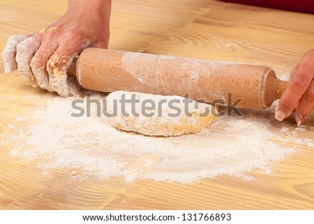 Working on unfinished dough with a rolling pin - stock photo