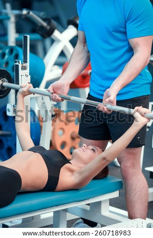 Working out. Concentrated young beautiful woman in sports clothing doing exercises in the gym with a barbell lying on the bench while her sports instructor controlling the workout - stock photo