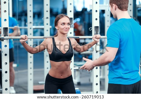 Working out legs exercises. Concentrated young beautiful woman in sports clothing doing exercises in the gym with a barbell while her sports instructor controlling the workout - stock photo
