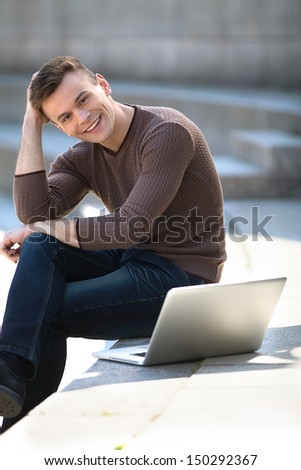 Working outdoors. Cheerful young man sitting near laptop and holding hand in hair - stock photo