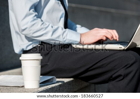 Working Outdoors. Cropped image of Cheerful businessman  using laptop  - stock photo