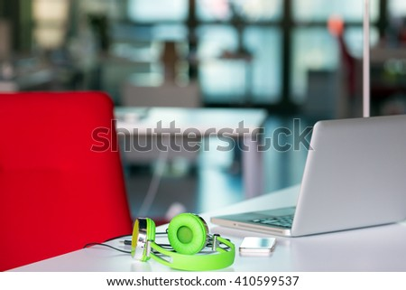 Working Place on grey Table with Laptop Computer green Headphones red Chair and Telephone in modern Office interior with large Window on Background - stock photo