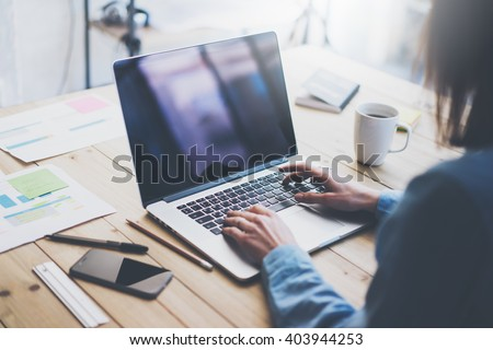 Working process photo.Woman working wood table with new business project.Typing contemporary laptop, reflections screen. Modern smartphone table.Horizontal.Film effect. Blurred background - stock photo