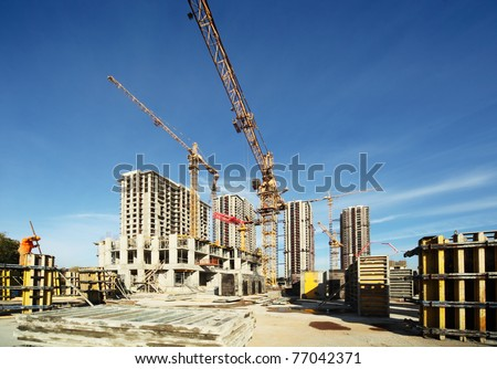 Working tall cranes inside place for with tall buildings under construction under a blue sky - stock photo