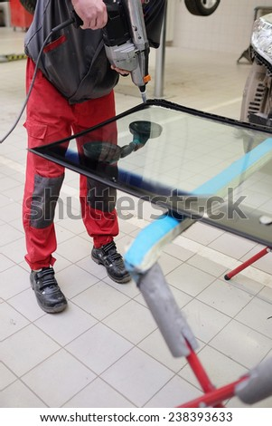 working to apply the adhesive sealant on the windshield - stock photo